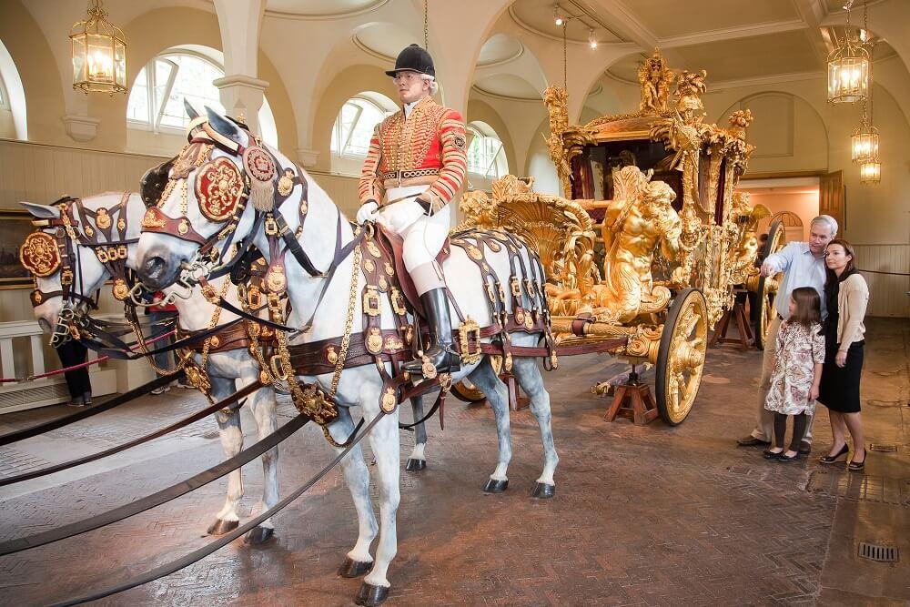 """מה לעשות בלונדון בחודש אוגוסט 2018 - ארמון בקינגהאם המלכה אליזבת - מבט מקרוב. כרכרה מוזהבת של בני משפחת המלוכה ב""""רויאל מיוז""""."""