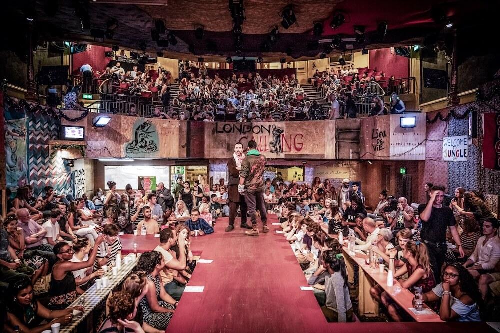 """הצגה בלונדון הג׳ונגל """"שחקני המשנה מסתובבים מדי פעם בקהל ונותנים פיתות, אורז ומנות אפגניות למי שנראה להם נחמד"""". במת תיאטרון הפלייהאוס שהפכה למסעדה אפגנית. צילום: Marc Brenner"""